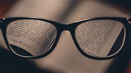 A close up photograph of a book viewed through reading glasses