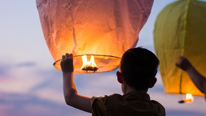 A photograph of a boy holding a Chinese style lantern