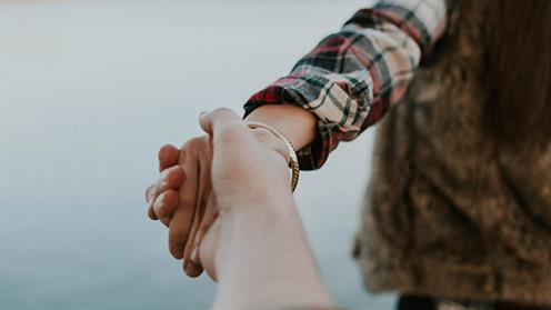A close up photograph of two people holding hands