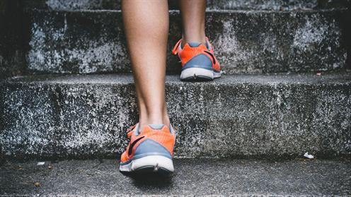 A close up photograph of a person in jogging shoes running up stairs