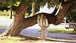 A photograph of a hand sculpture holding up a tree