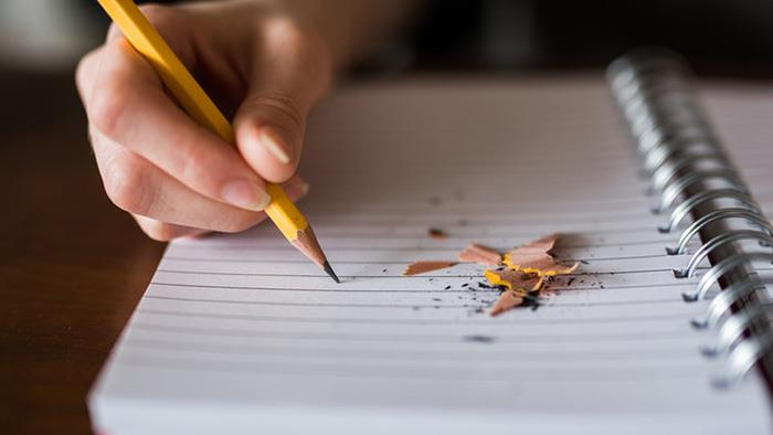 A close up photograph of a person writing in a notebook with a pencil