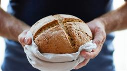 A photograph of artisan bread in the hands of a person