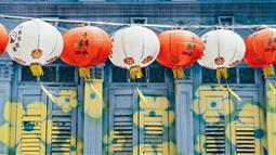 A photograph of some Chinese lanterns against a painted wall of flowers. Image by Annie Spratt courtesy of unsplash.com.