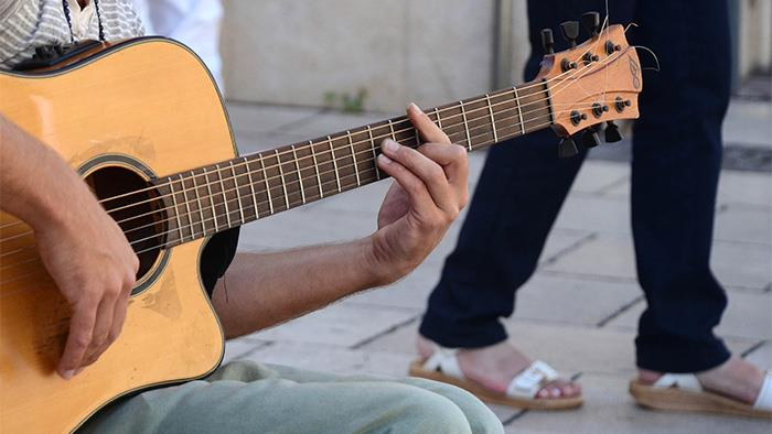 Person playing guitar outdoors.