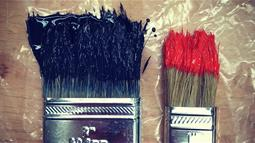 A photograph of paintbrushes loaded with blue and red paint