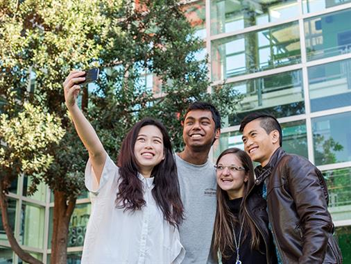 A photograph of a group of young people taking a selfie