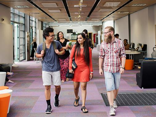 A photograph of three young people walking in a building