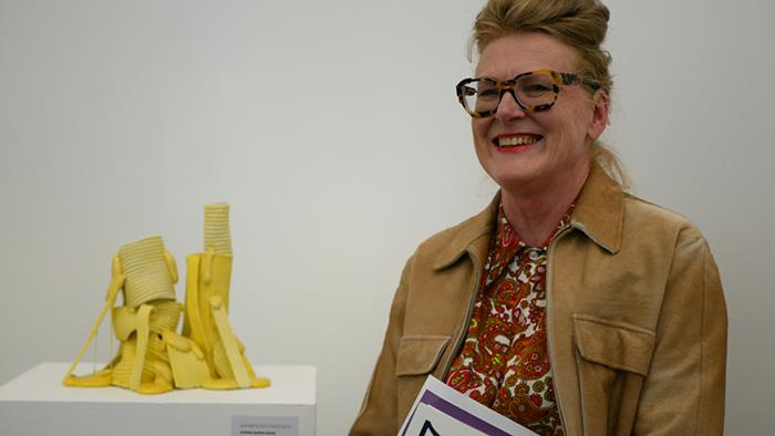 A photograph of Andrea du Chatenier with her art work Yellow Stack