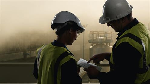 A photograph of two people in high vis clothing and helmets on a geothermal work site.