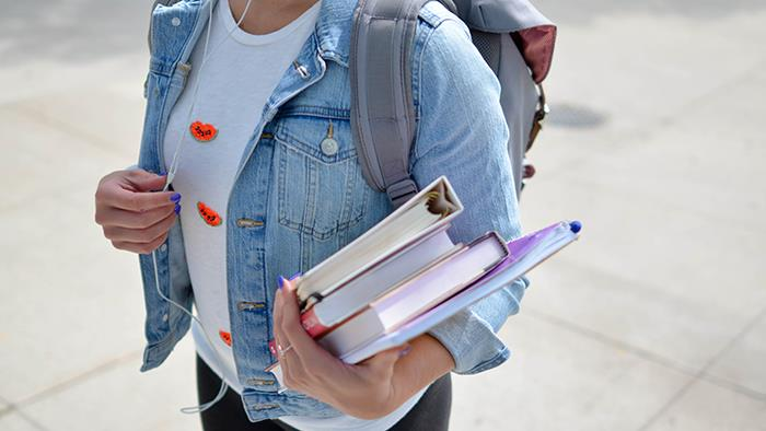 A photograph of a student carrying books