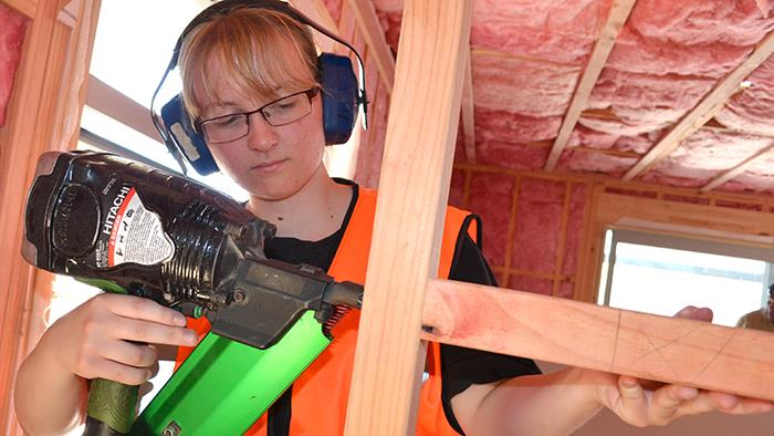 A photograph of a young lady using a nail gun to construct a wall in a house