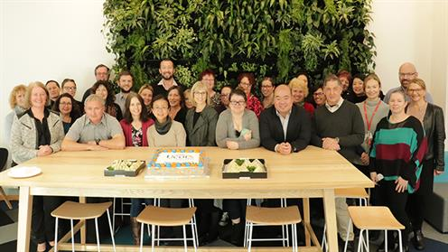 A photograph of a group of UCOL staff with a cake at the information centre in Palmerston North