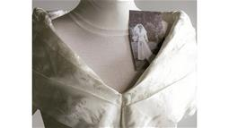 A close up photograph of a wedding dress that has been refashioned, with a photograph inserted of the original garment.