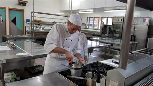 A chef cooking a dish in a commercial kitchen