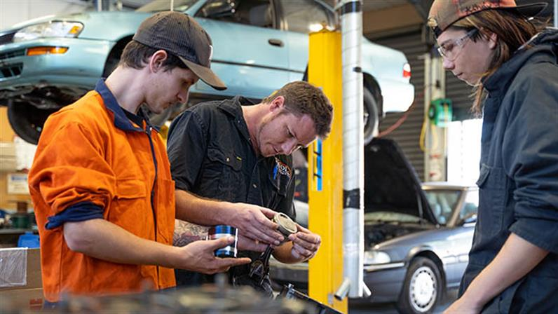 A photograph of two young people looking under the bonnet of a car in a workshop at UCOL.