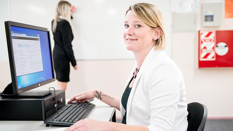 Lady sitting at a computer in a classroom