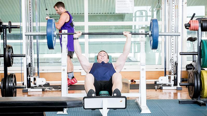 Exercise and Sport Science student lifts weights in the Palmerston North campus gym