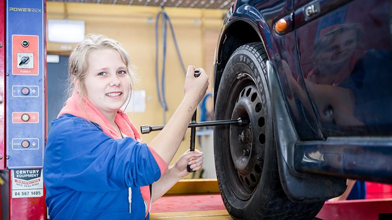 A lady changing a tyre in a workshop