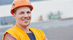 A photograph of a man in a hard hat on a works site