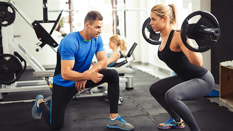 A photograph of a trainer with a client in a gym