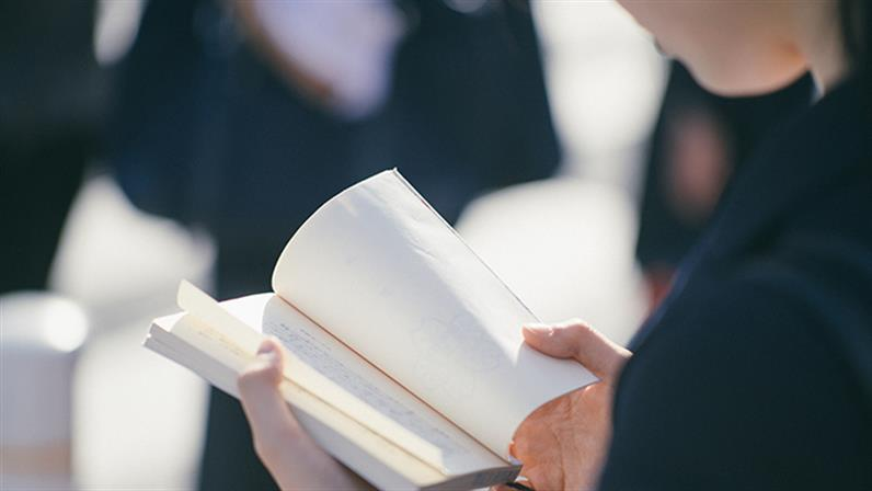 A close up photograph of a person reading a book