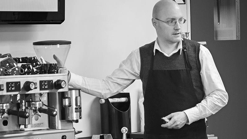 A person demonstrating barista skills with a coffee machine