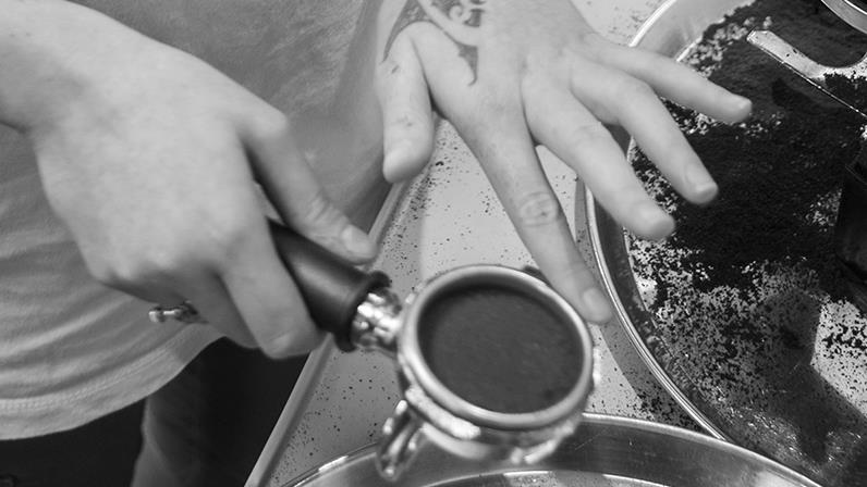 Detail image of coffee being tamped