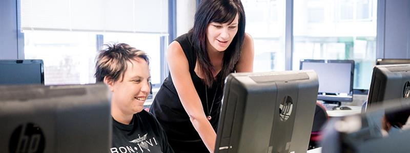 A photograph of two women looking at a computer screen