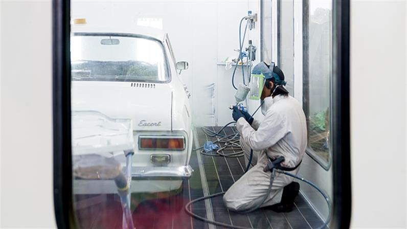 A student spray painting a car