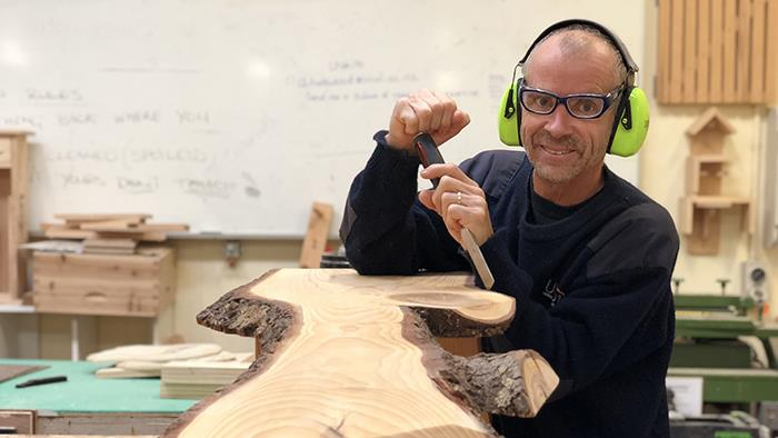 A photograph of UCOL Furniture Design Staff member Andy Halewood in a workshop working on a piece of furniture for charity.
