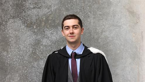 Portrait of Chris Percy in a graduation gown