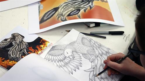 A close-up photograph of a student sketching a bird