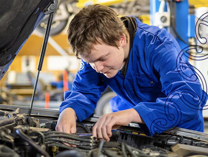 A photograph of two young people looking under the bonnet of a car in an automotive workshop at UCOL