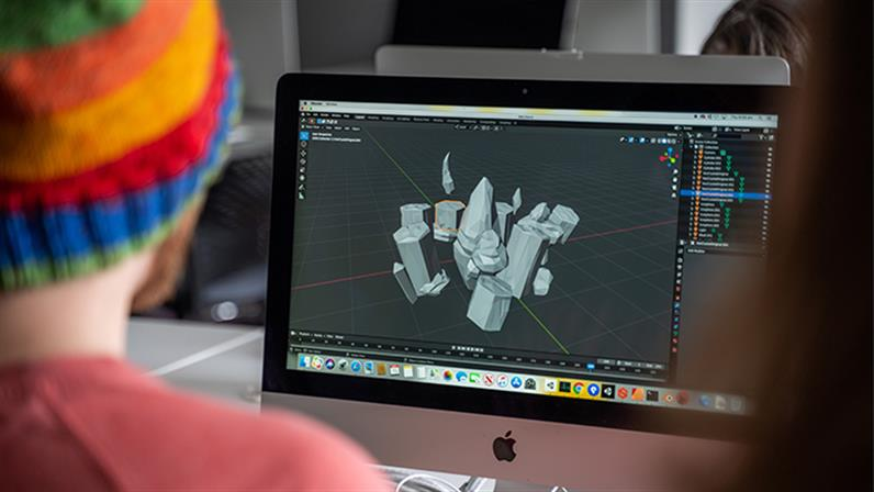 A photograph of a student works on a Mac at the Whanganui School of Design