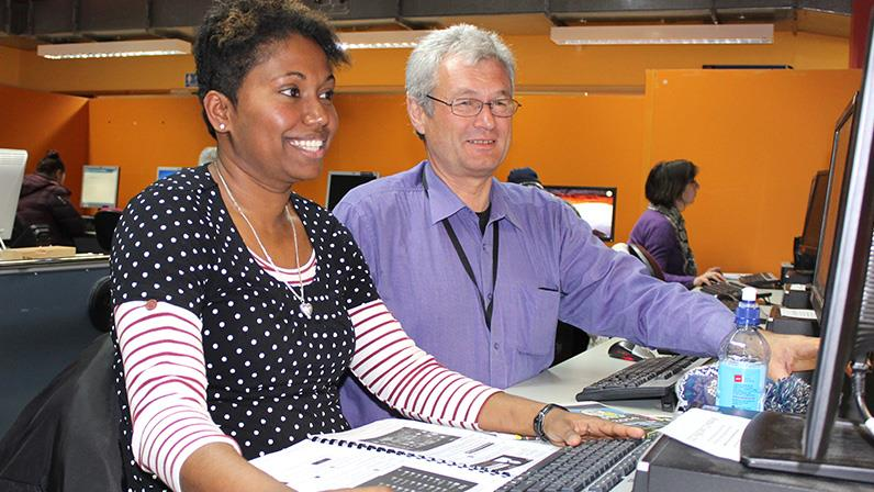 A photograph of a lecturer instructing a lady at the computer lab
